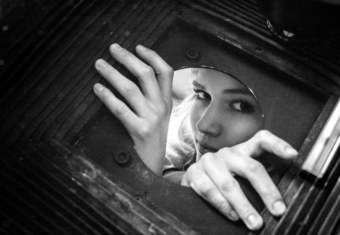 Frau schaut durch ein Loch