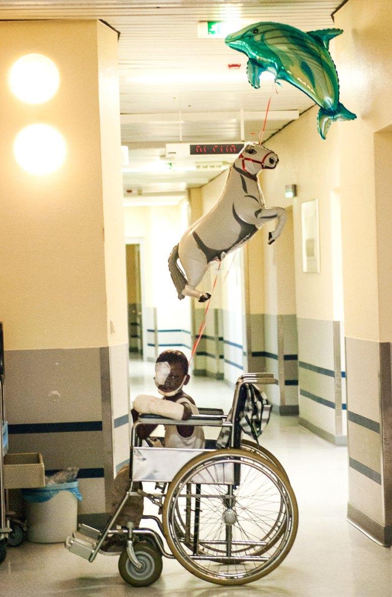 Kind auf einem Rollstuhl mit Tier-Luftballons