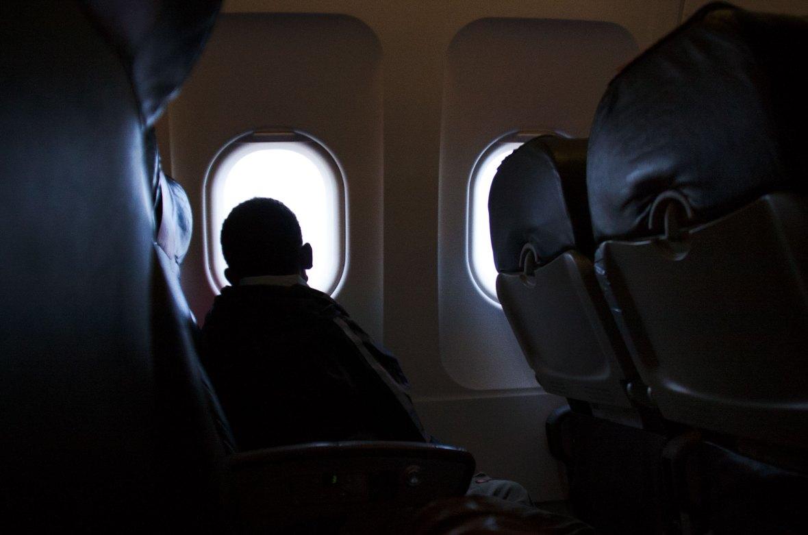 Kind im Flugzeug schaut aus dem Fenster