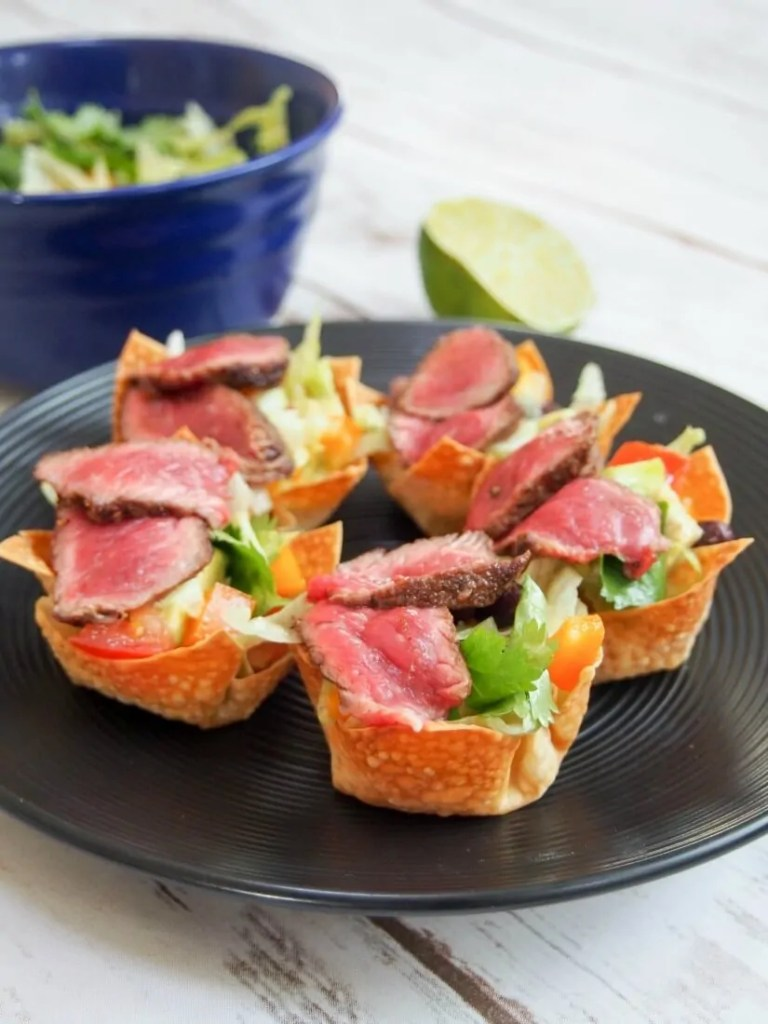 These steak taco salad wonton cups are perfect handheld bites of delicious Tex-Mex salad in a crunchy wonton cup. A great gameday snack, impressive party appetizer or any excuse. Pretty healthy too!