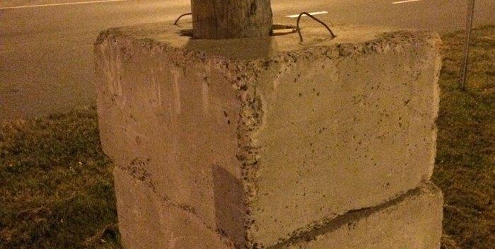Poteau électrique enraciné dans le béton