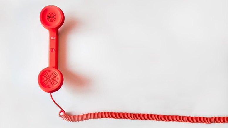 Combiné de téléphone rouge sur fond blanc