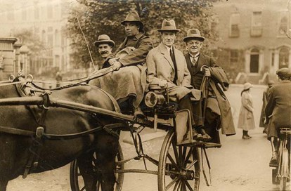 Perched at the back of this jaunting car (holding the umbrella) is the Right Honourable F.O. Roberts, M.P. and British Minister for Pensions, apparently enjoying a ride around St. Stephen's Green.  Date: 9 December 1924