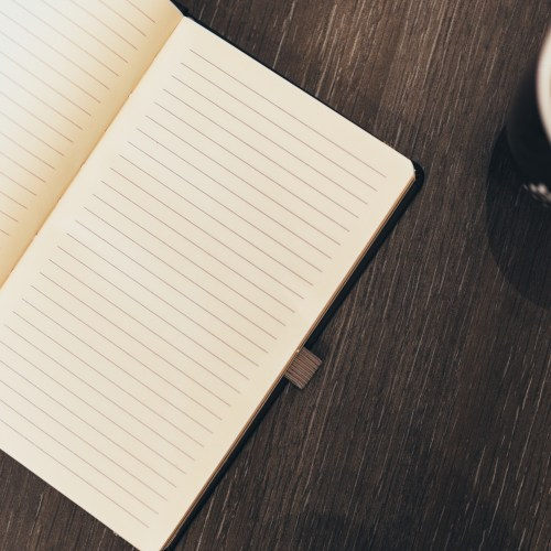 Open notebook on wooden table with coffe mug