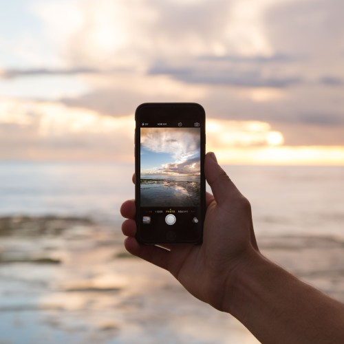 An iPhone being helpd up to take a picture of the ocean.