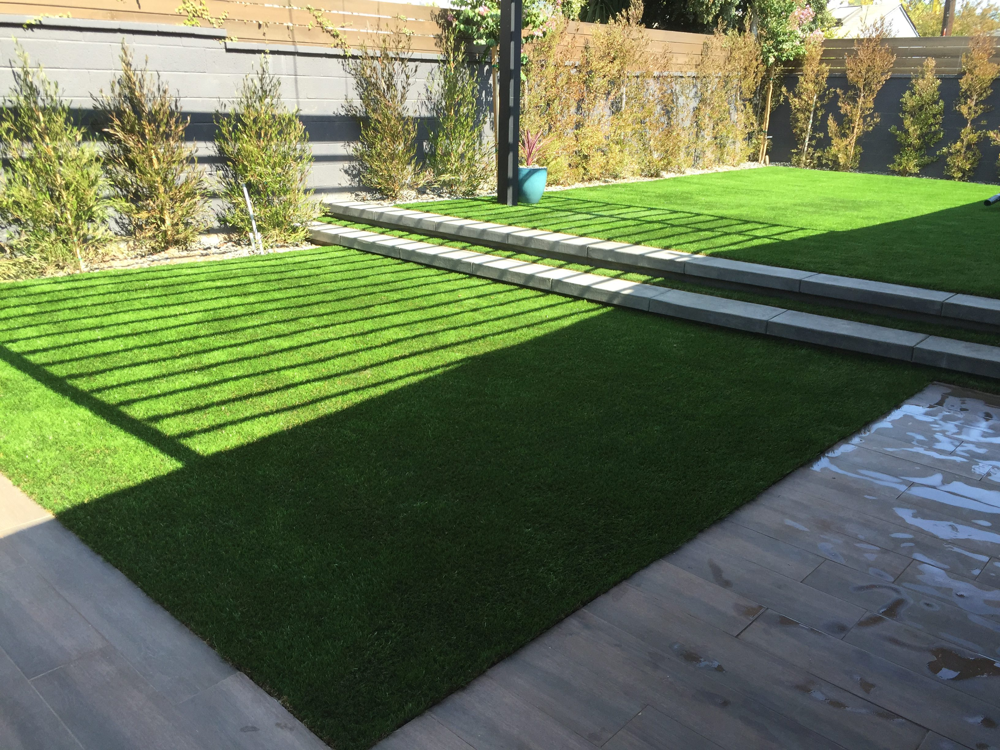 backyard renovation in the city of West Los Angeles - Concrete steps, Synthetic turf and wood tile.