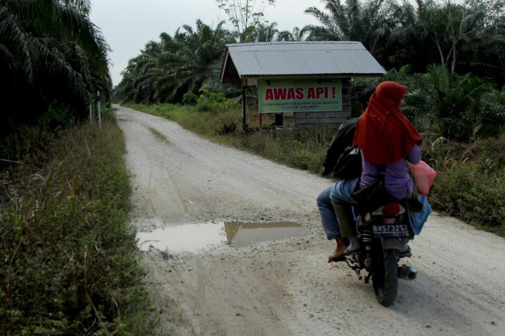 """Un cartel reza """"Cuidado, fuegos"""" cerca de Dosan, un pueblo que está luchando contra los incendios en la isla de Sumatra, Indonesia."""