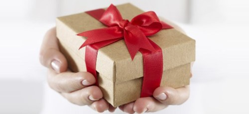 Hand holding a brown gift box with red ribbon (Photo from Mashable.com)
