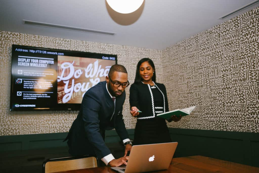 man and woman in conference room looking at a laptop moving career forward
