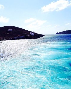 blue water off the back of a ferry in greece looking at an island with a small white church