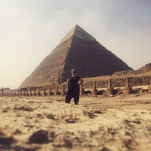 Carry On Or Bust travel blogger standing infront of the pyramids of giza in egypt