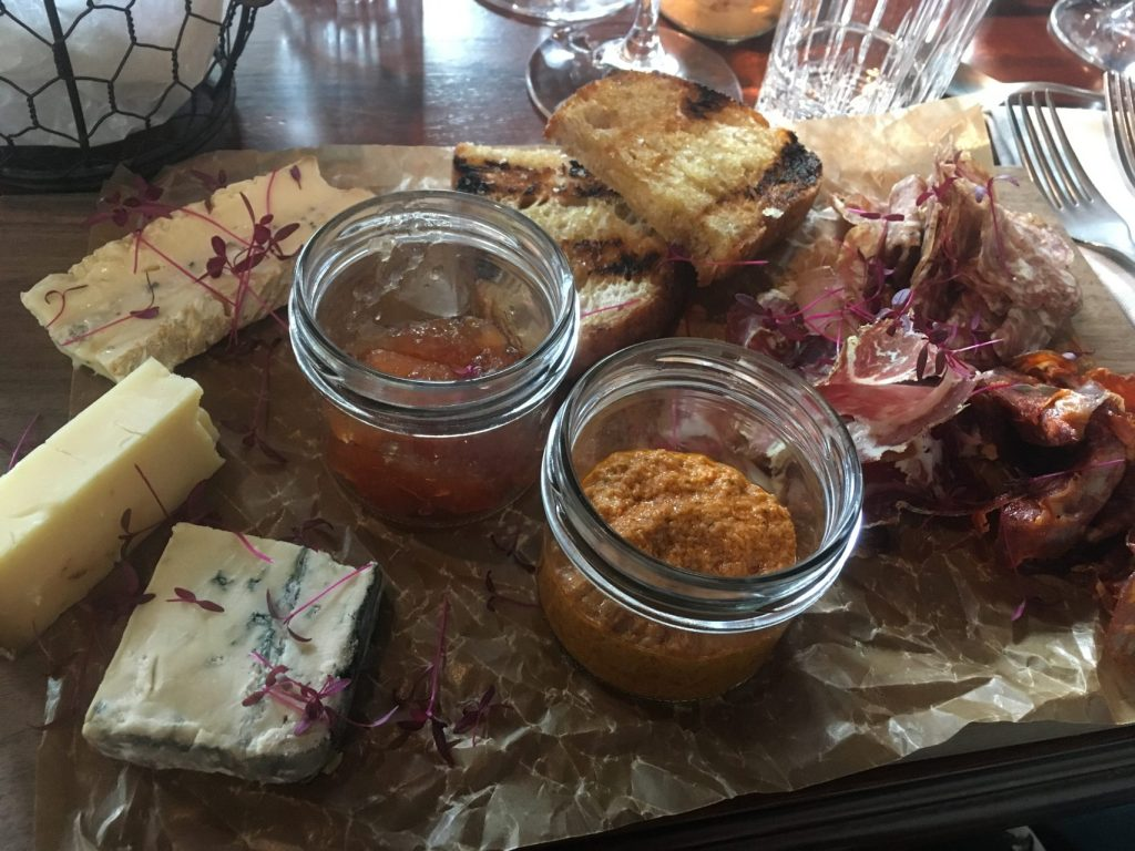 Chamberlain grill starter, Smoked Meat and Cheese on a wooden board with condiments Steam Hotel