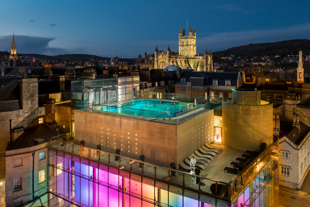 exterior of thermae bath spa showing coloured lights and rooftop pool
