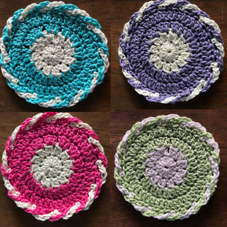 four crocheted coasters in blue, purple, pink and green