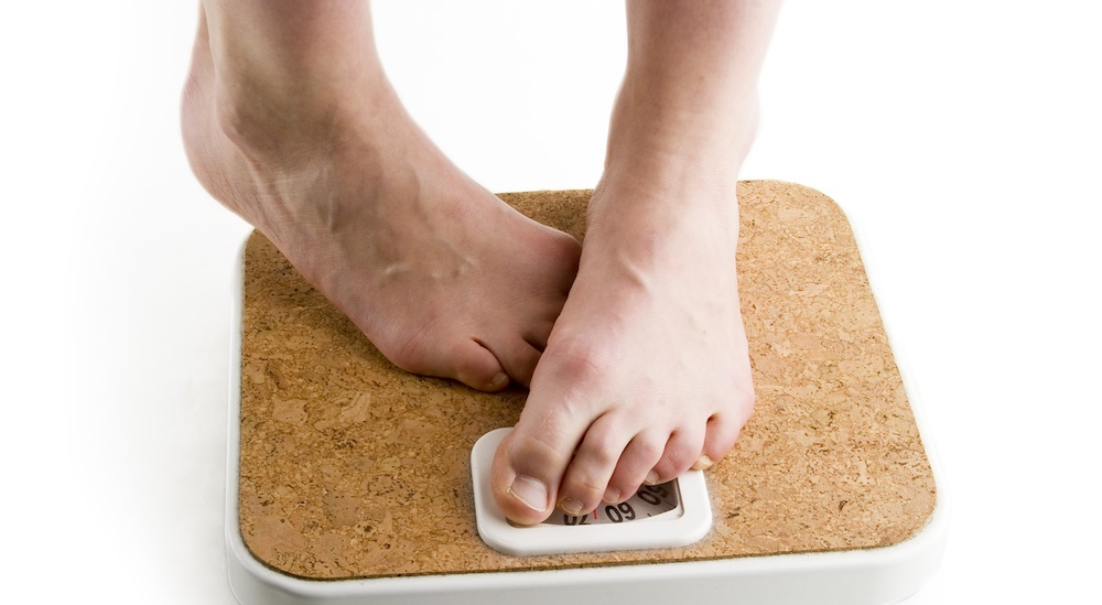 a pair of female feet standing on a bathroom scale looking shy about the weight