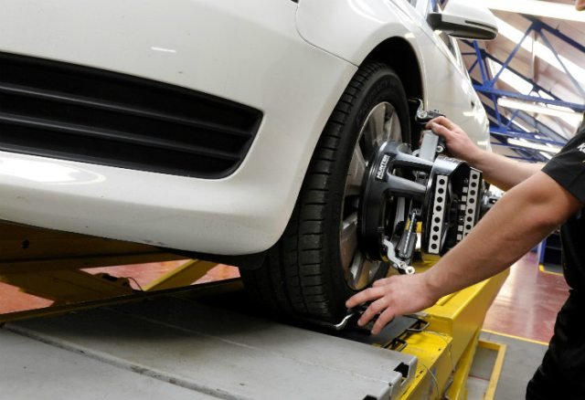 Technician-performing-a-wheel-alignment-check