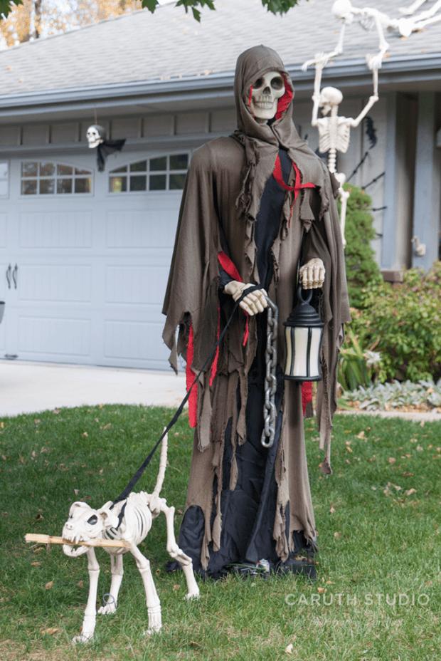 Grim Reaper with lantern walking a skeleton dog