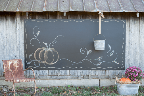 Outdoor chalk board with a pumpkin and pail, situated between flowering Mums and a patina'd outdoor metal chair