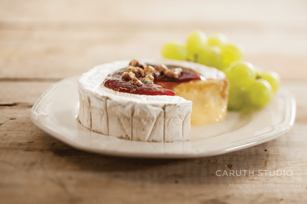 Bourbon Plum Jam on brie cheese with grapes accompanying