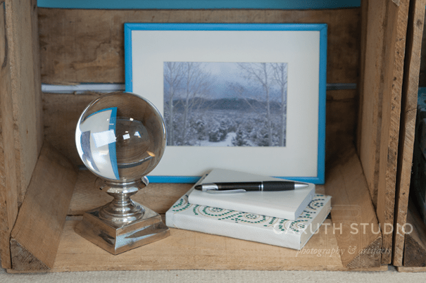 Photo and journal and pedestaled glass globe in wooden crate