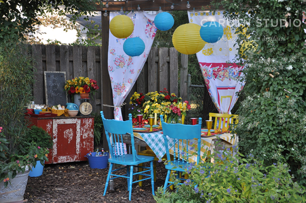 Retro party with lanterns, tables and chair, buffet cart and curtains hanging from the pergola