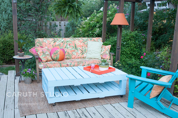 Pallet table on deck in front of a couch and deck chair
