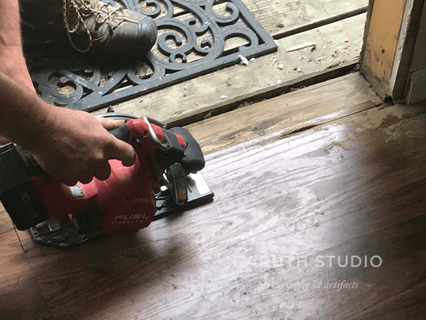 sanding the wood boards below door threshold