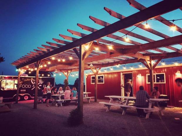 Ciderworks lite patio in the evening with picnic benches, a pergola and red drinking trailer