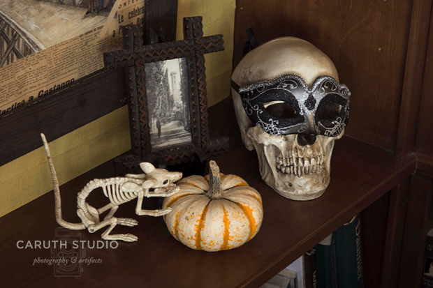 rat skeleton eating a pumpkin next to a skull with a masquerade mask