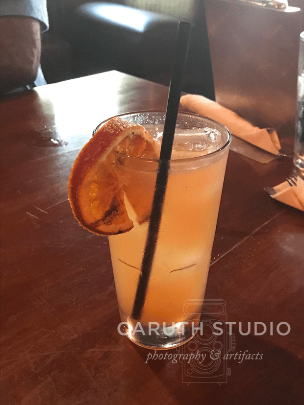yummy cocktail in a tall class with a caramelized orange slice for garnish