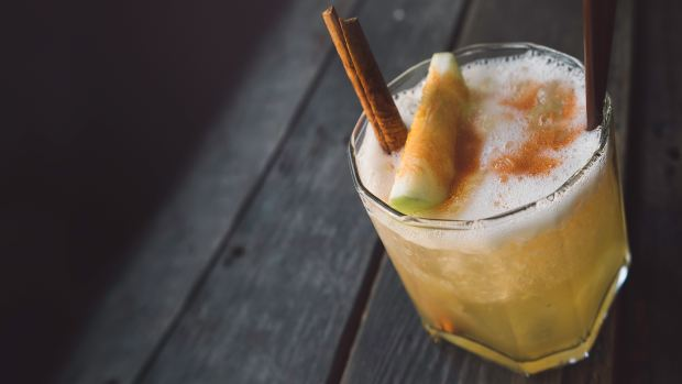 apple punch in a chilled tumbler with apple slice and cinnamon stick for garnish
