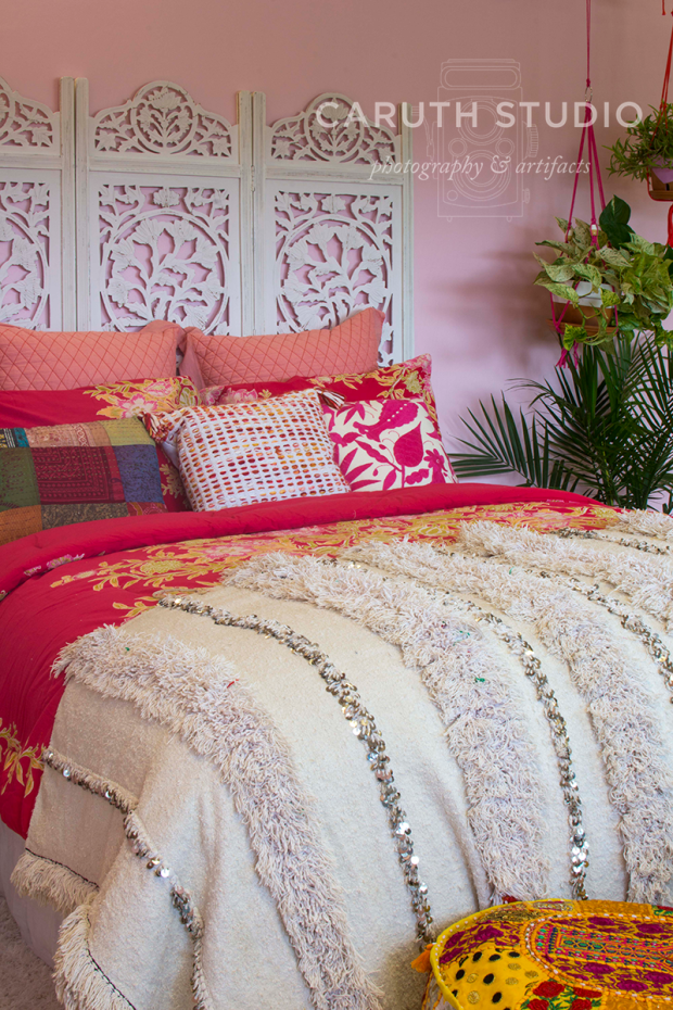 shades of pink beding and white throw and coordinating white wooden carved screen headboard and hanging green plants in the background
