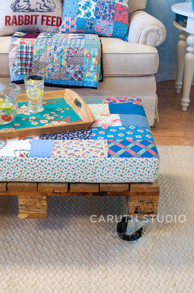 pillow topped coffee table and teal-floral pattern tray with drinking glasses