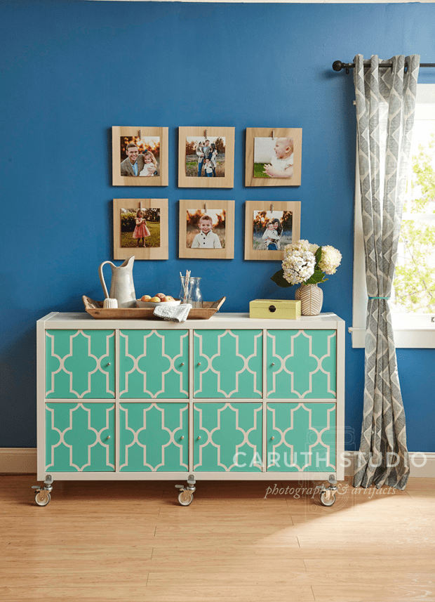 Grid of wood plaque photos on a blue wall above a green and white buffet