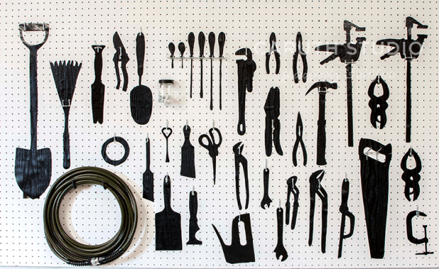 Tool pegboard with shadow prints of hanging tools