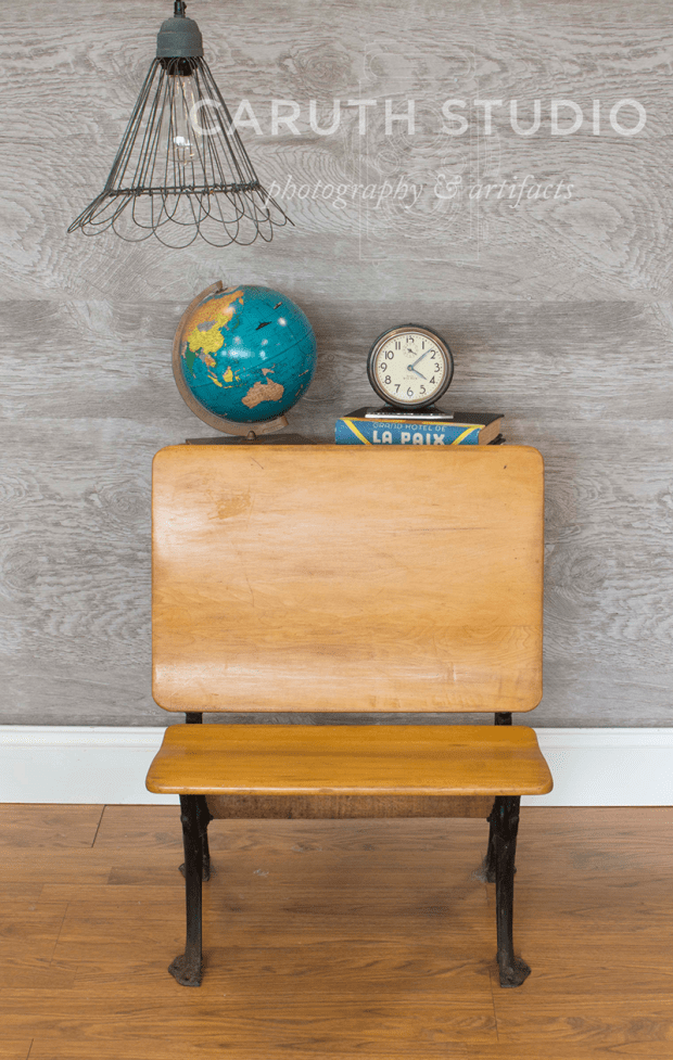 vintage desk nightstand with a globe, stack of books and clock with basket lantern hanging from ceiling