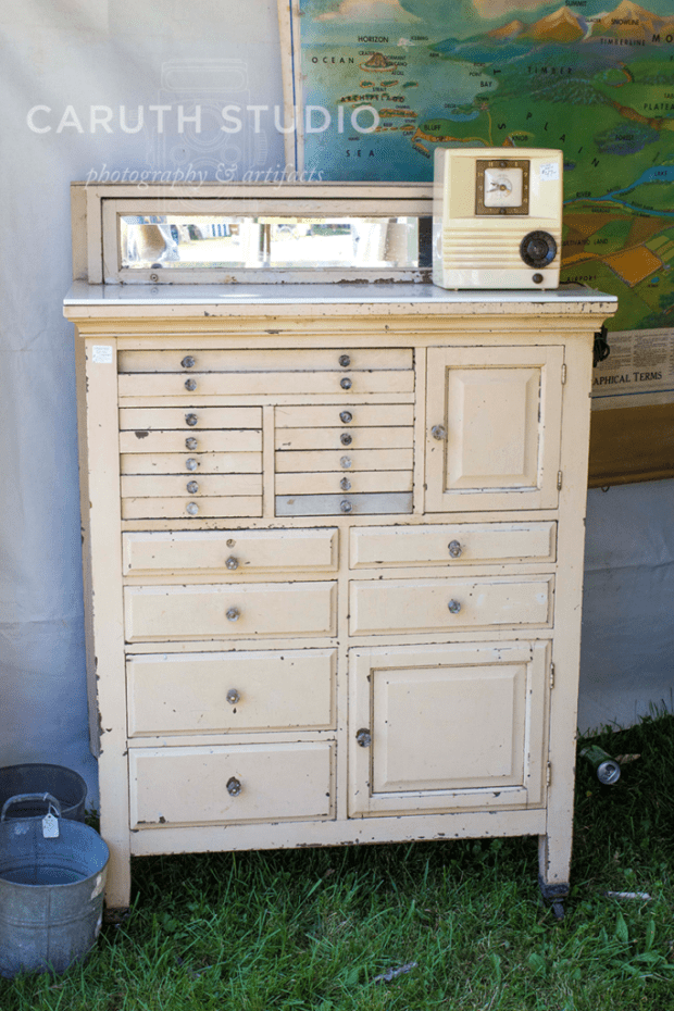 vintage white tall cabinet on caster wheels topped with a short mirror