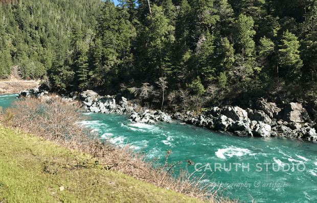 Smith River flowing strongly between bank and rocks
