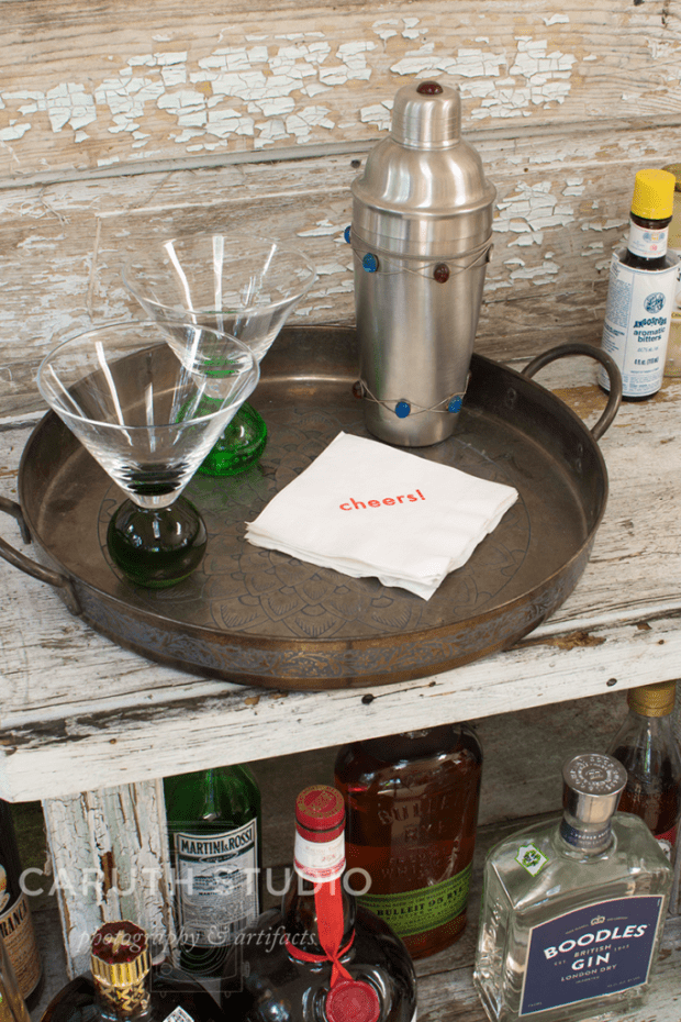 silver tray with a cocktail shaker and two martini glasses on repurposed door bar