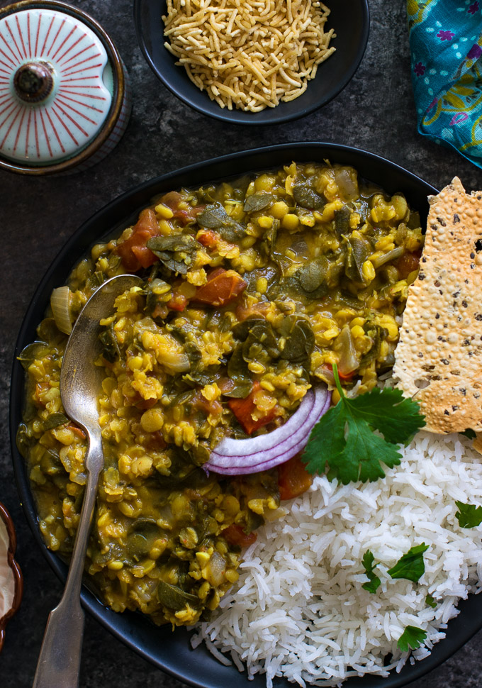 Dal rice on a black plate with bhujia sev