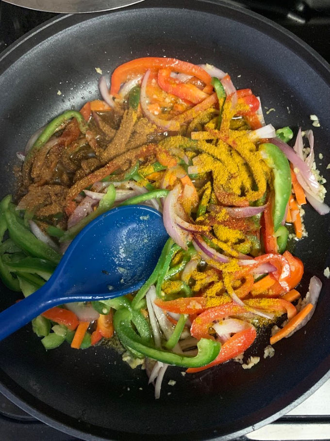 Adding masalas in the pan to cook vegetable jalfrezi.