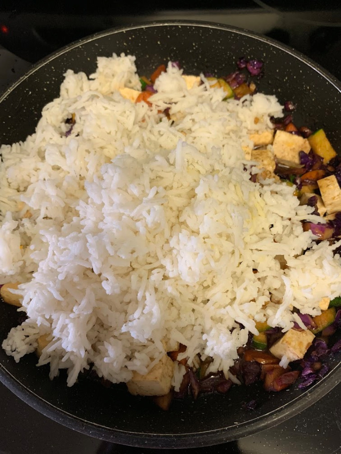 Adding rice to the pan.
