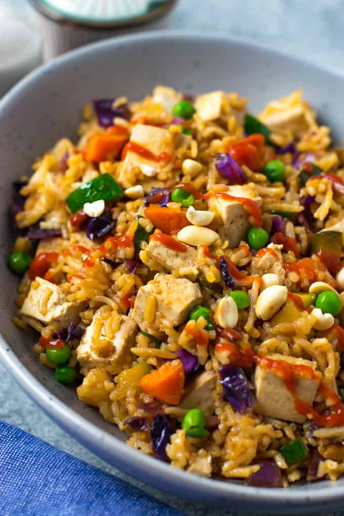 Vegetable fried rice drizzled with hot sauce.