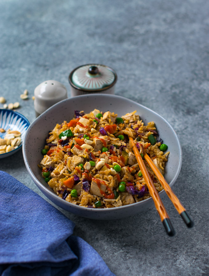 Vegetable tofu fried rice in a bowl with chopsticks.
