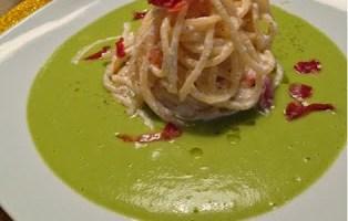 Spaghetti quadrati con ricotta e pancetta croccante su vellutata di piselli
