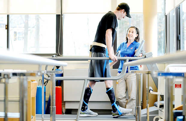"""Nate Clark of Dixfield works with his physical therapist, Sophie Herr, at the New England Rehabilitation Hospital of Portland. Clark suffered a spinal cord injury during a snowmobile hill climb race at Black Mountain ski area on Jan. 11. He is able to use his legs, but not nearly to the extent that he could before the accident. """"Nate has to teach his brain to use his legs in a different way,"""" Herr said. Clark has physical therapy once a week."""
