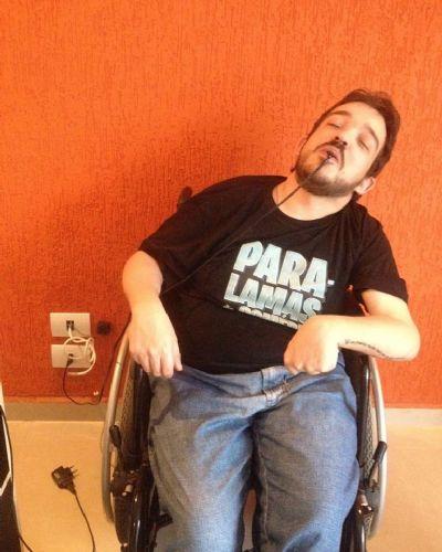 A imagem está no formato retangular na horizontal. Nela contém o comediante Paulo Fabião sentado em sua cadeira de rodas, encostada em uma parede de cor laranja. Com um carregador de celular na boca que está ligado a uma tomada ao seu lado. Como se estivesse carregando as energias. Fim da descrição.