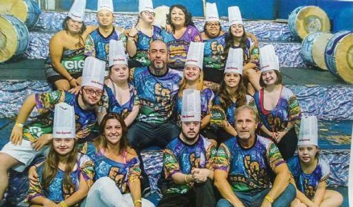 A imagem está no formato retangular na horizontal. Nela contém participantes do dos Chefs especiais reunidos para a foto na quadra da escola de samba rosas de ouro e o chefe Henrique Fogaça está no meio deles. Todos estão vestidos com a camiseta da escola de samba e com um chapéu de cozinheiro. Fim da descrição.
