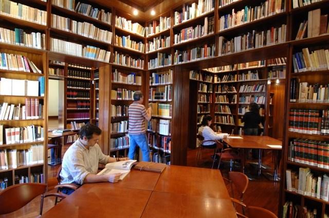 Foto de uma biblioteca, com várias estantes cheias de livros do chão ao teto. Há mesas e cadeiras, com pessoas lendo