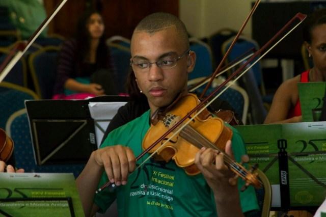 Moséis começou a tocar violino com 7 anos e o uso do aparelho amplificador sonoro e do sistema FM facilitaram a aprendizagem tanto na escola como na música (Foto: Marta Amancio / Arquivo pessoal )